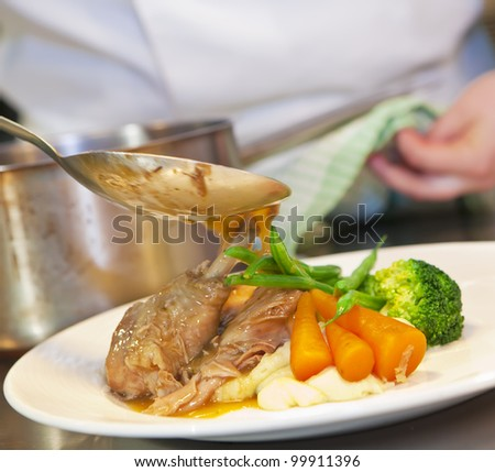 Closeup of chef pouring hot sauce on his dish. Finishing touch before dish goes on the table. Square crop. - stock photo