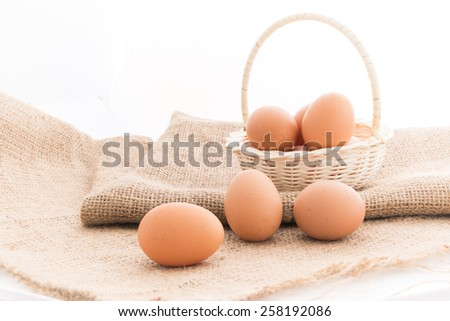 Closeup of Chicken eggs in the bamboo basket over sackcloth - stock photo