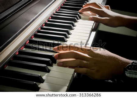 Closeup of child's hands playing the piano - stock photo