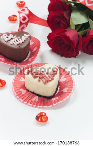 Closeup of chocolate and vanilla petite cheesecake for Valentine Day. Bouquet of red roses.