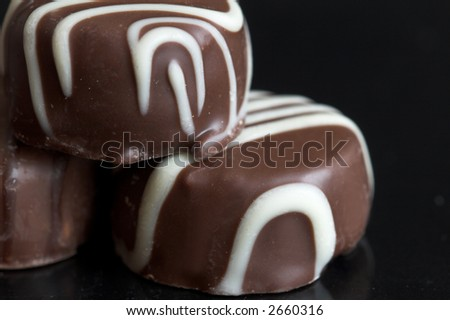 Closeup of chocolates on black background - stock photo