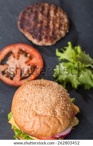 Closeup of classic burger with ingredients top view on black - stock photo