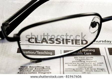 Closeup of classified ads in newspaper with reading glasses. - stock photo