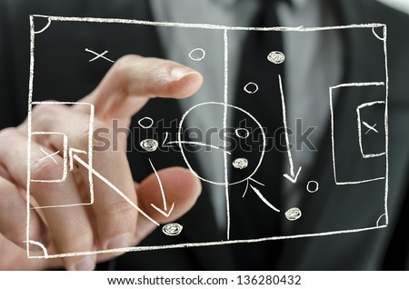Closeup of coach pointing to a football strategy plan drawn on a virtual screen. - stock photo