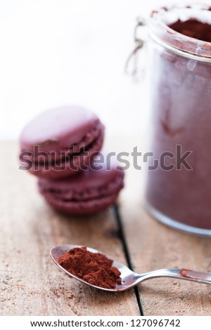 Closeup of cocoa powder in spoon with two macaroons and glass jar in background