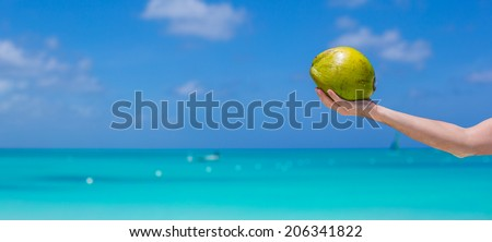 Closeup of coconut in hands background the turquoise sea