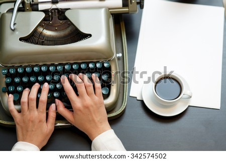 closeup of coffee and hands writing on old typewriter  - stock photo