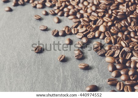 Closeup of coffee beans on natural stone surface. Heap of seeds on grey texture with copy space, soft color toning - stock photo