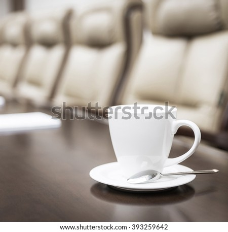 Closeup of coffee cup on table in empty corporate conference room before business meeting in office