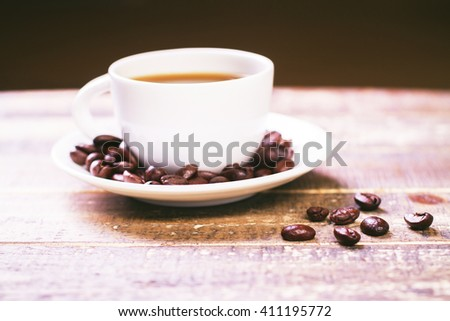 Closeup of coffee cup with beans on saucer and wooden table - stock photo