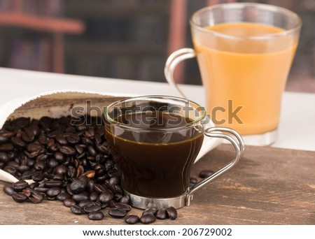 closeup of cofffe cup and coffee beans with a latte on the background selective focus - stock photo