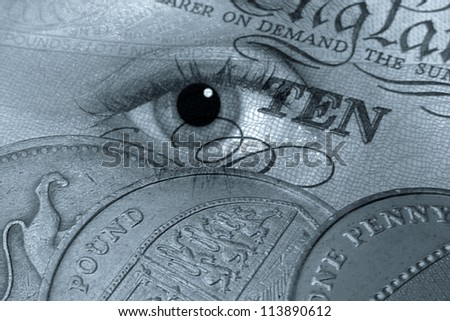 Closeup of coins on banknote overlaid with eye. - stock photo