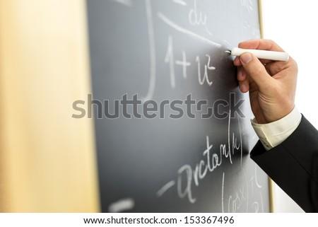 Closeup of college math professor writing complicated equation on black board. - stock photo