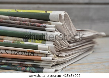 Closeup of color stacked  journal newspapers on a wooden table background - stock photo
