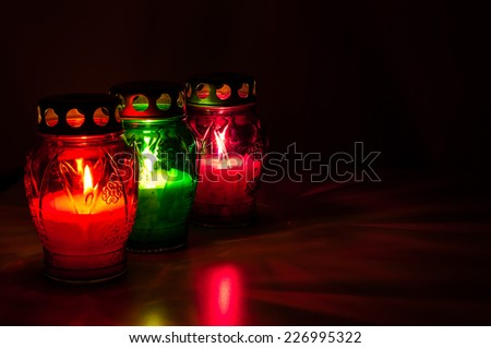 Closeup of colored burning votive candles in the dark - stock photo