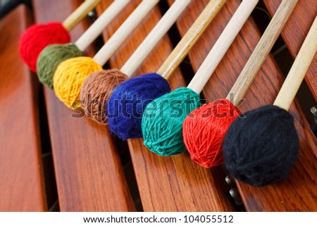 Closeup of colored mallets on a wooden marimba - stock photo