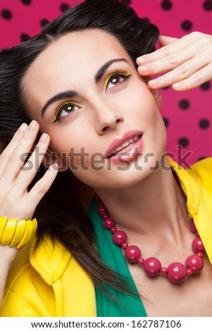 Closeup of colorful fashion shot of model with yellow eyelids, pink lips, yellow jacket, polka background - stock photo
