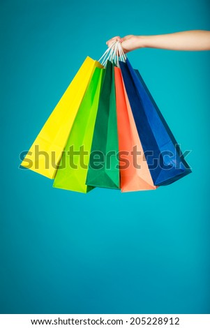 Closeup of colorful paper shopping bags in female hand on vibrant blue. Woman girl buying clothes. Sale and retail. - stock photo