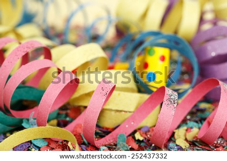 closeup of colorful party streamers on confetti - stock photo