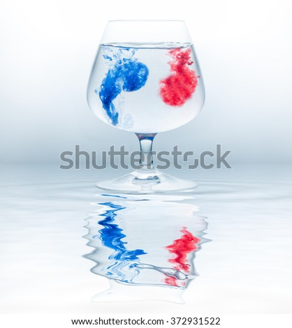 closeup of colorful water drops in cogna glass - stock photo