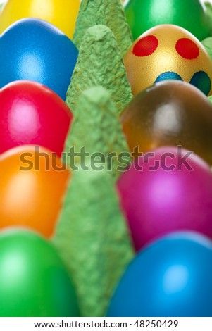 Closeup of colourful Easter eggs in egg box. Only one egg has dots.