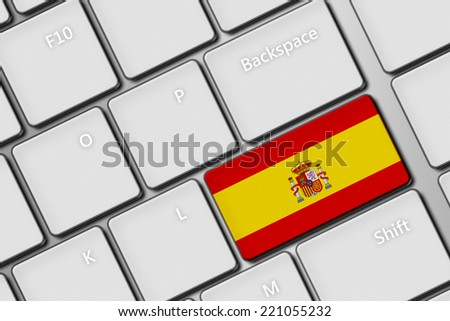 closeup of computer keyboard with spanish flag button - stock photo