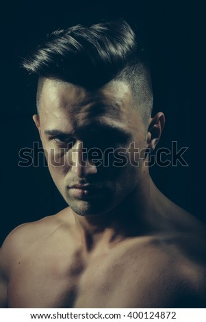 Closeup of confident fearless cool hot sexy handsome charming young brunet guy with short hair looking straight having broad bare shoulders posing on black background indoor upper half portrait - stock photo
