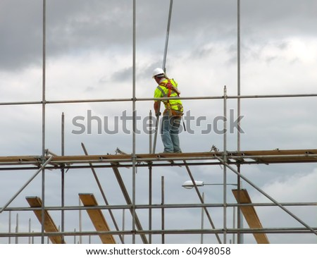 Closeup of construction worker assembling scaffold on building site - stock photo