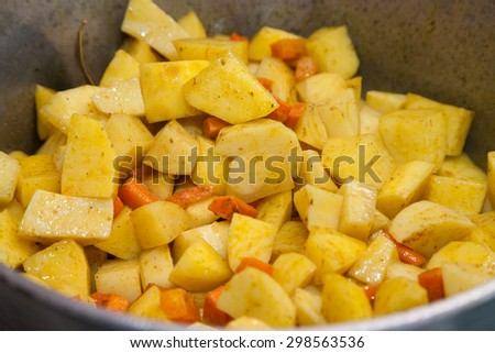 Closeup of cooking roasted potatoes with carrots - stock photo