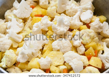 Closeup of cooking roasted potatoes with cauliflower - stock photo