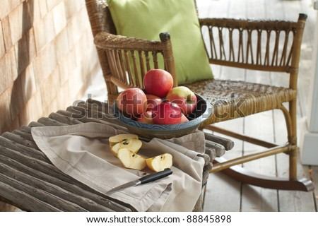 Closeup of country porch outdoors with apple still life on rustic table and antique rocking chair. Cedar shingles in background. Horizontal format and copy space. - stock photo