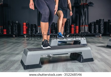 Closeup of couple legs over step boards training in aerobic class on a fitness center. Sport and health concept. - stock photo