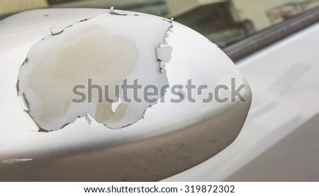 Closeup of cracked and peeling paint on an old car window. - stock photo