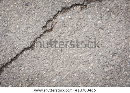 closeup of cracks on asphalt road.