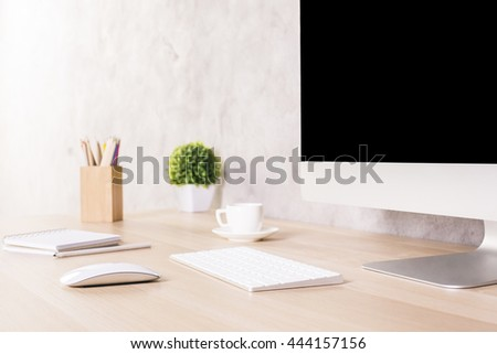 Closeup of creative designer desktop with blank computer monitor, keyboard, coffee cup, stationery items and plant on concrete wall background. Mock up - stock photo