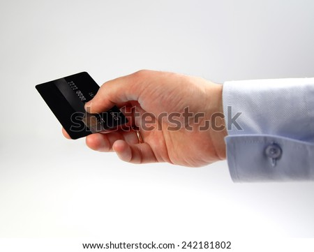 closeup of credit card holded by hand, captured with small depth of field. Focus on credit card - stock photo