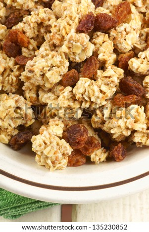 Closeup of crunchy oat clusters with raisins served in a bowl for an healthy breakfast.