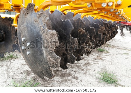 Closeup of cultivator knives of plowing tractor with dirt and selective focus - stock photo
