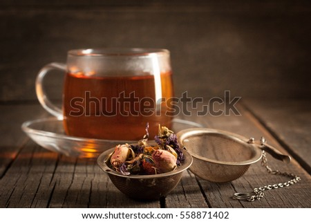 Closeup of cup of tea with tea leaves, mint on vintage wooden background. Black herbal tea with lemon, ginger and honey. hot winter drink