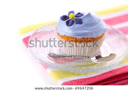 Closeup of cupcakes decorated with candied violets from flower on white background isolated