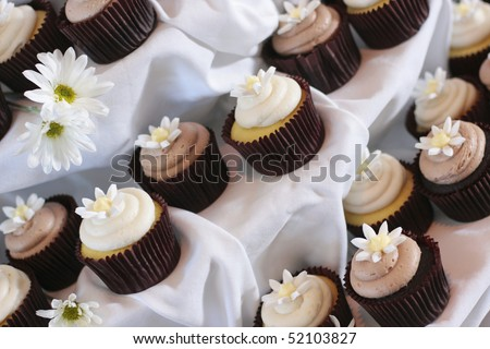 Closeup of cupcakes with flowers at fancy party - stock photo