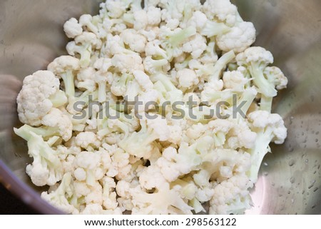 Closeup of cut cauliflower in stainless steel bowl - stock photo