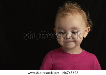 Closeup of cute baby boy looking down on black background - stock photo