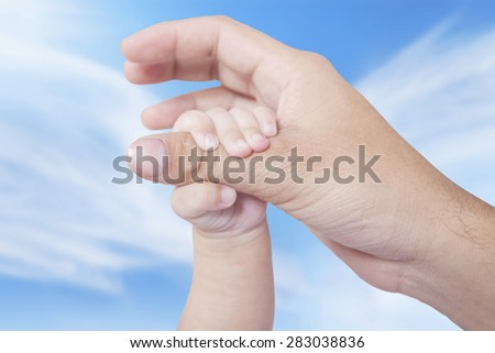 Closeup of cute infant hand holds father finger, shot outdoors under clear sky - stock photo