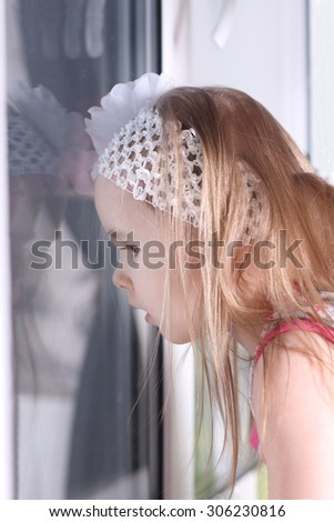 Closeup of cute little blond girl with white bandage looking out window - stock photo