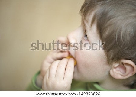Closeup of cute little boy looking up while eating in house - stock photo
