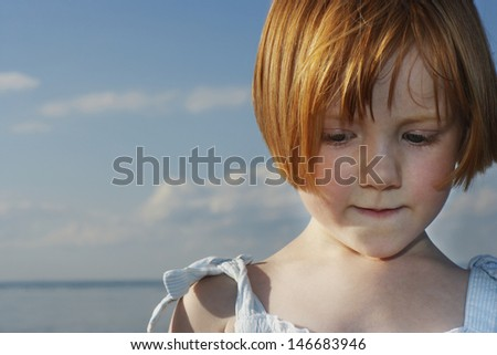 Closeup of cute little red haired girl looking down at beach - stock photo