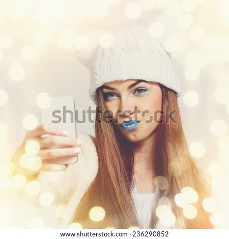 Closeup of cute teenage girl with beanie hat and blue lipstick taking a selfie with smart phone. Beautiful young woman with makeup photographing herself with smartphone. Square format image. - stock photo