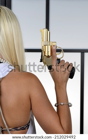 Closeup of dangerous young blonde woman with the bared shoulders holding golden revolver handgun. - stock photo