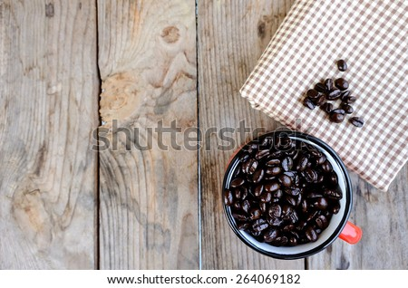 closeup of dark roasted coffee beans in red cup on the wooden table with fabric, focus on coffee beans in red cup - stock photo